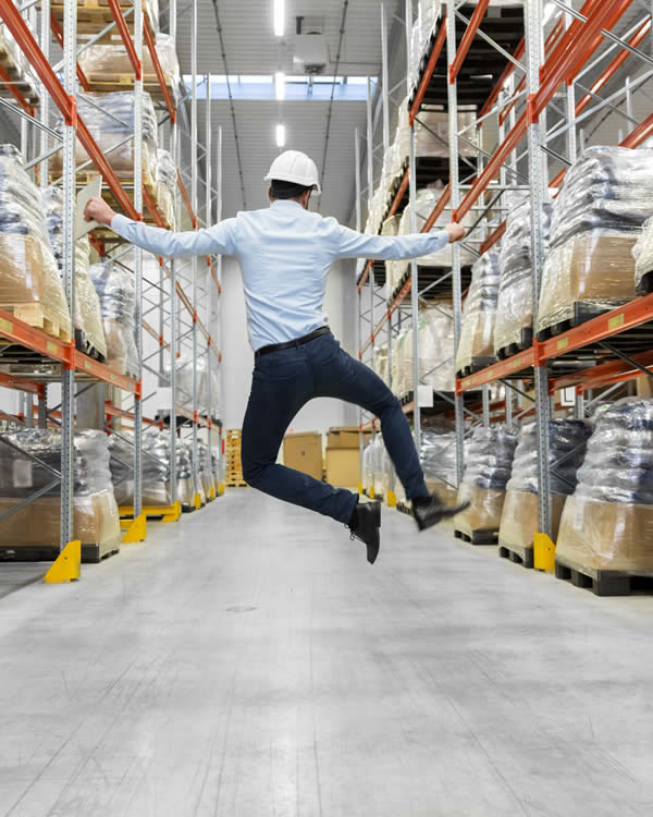 homme heureux de profiter des avantages du déstockage d'un stock en fin de vie ou de fins de série dans un entrepôt plein de cartons de marchandises obsolètes