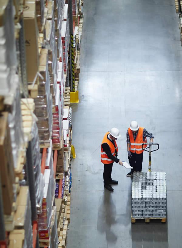 experts du destokage qui montrent des marchandises emballées sur des palettes portées par un chariot élévateur dans un entrepôt de stockage