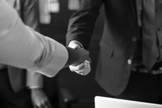 destockeur qui sert la main à une personne venant de lui vendre son stock de produits issus de la concurrence