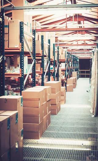 des cartons de textile sur des étagères dans un entrepôt d'une entreprise de déstockage