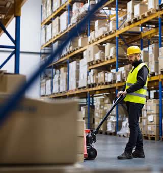 soldeur destockeur qui tire un transpalette rempli de cartons de produits d'une entreprise en liquidation
