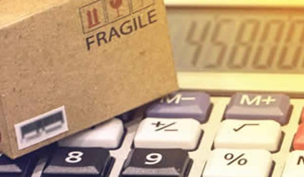 gestion des coûts de stockage avec des petits cartons et une calculatrice pour contrôler les frais de stockage