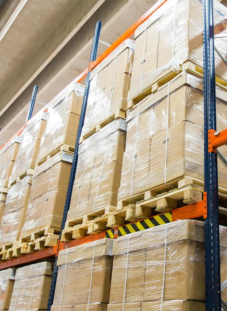 palettes de marchandises en surproductions stockées dans des cartons sur des étagères d'entrepôt de destockage