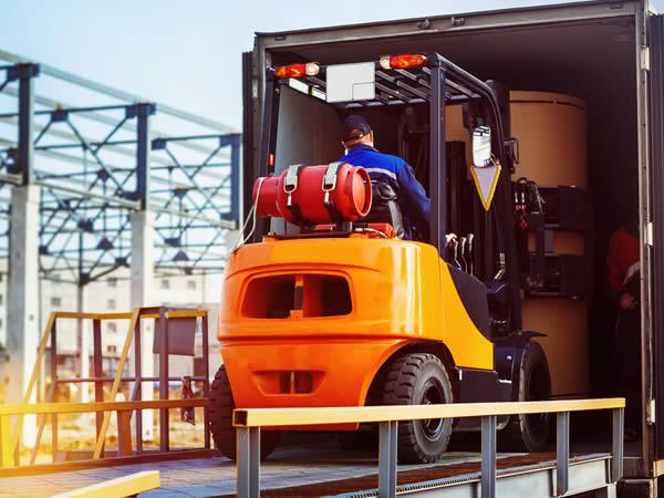 soldeur destockeur qui entre dans un camion sur un chariot élévateur