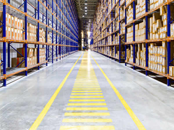 Rangées d'étagères remplies de cartons de produits en fin de vie dans un entrepôt d'une entreprise de destockage de marchandises obsolètes