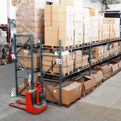palettes de marchandises et cartons de produits dans un grand entrepôt de destockage