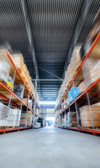 Grand hangar d'un entrepôt de destockage avec des étagères hautes pour le stock d'une entreprise en faillite