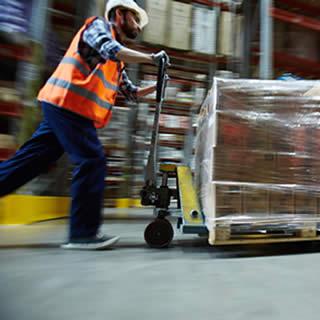 soldeur qui pousse rapidement un charriot elevateur contenant des cartons de produits rachetés suite à un sinistre de transport